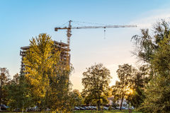 Urban housing construction. Tower crane with a multi-storey building under construction in the evening among autumn trees