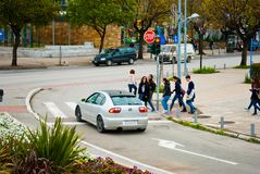 Full length of young people crossing the road on zebra crossing stock image