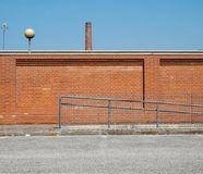 Urban industrial background. A brick wall with an old factory chimney in front of a concrete road. Old urban industrial background. A brick wall with an old royalty free stock photography