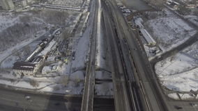 Urban industrial city. Aerial view on the road and railways. Urban landscape in winter season. Train and cars are going by the town stock footage