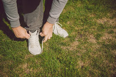 Urban jogger tying his running shoes. On a green grass Stock Images