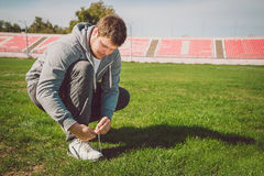 Urban jogger tying his running shoes. On a green grass Royalty Free Stock Image