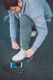 Urban jogger tying his running shoes. With phone on the ground Royalty Free Stock Images