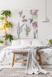 Urban jungle bedroom interior with a bed dressed in white and green bedding and painted art on the wall royalty free stock image