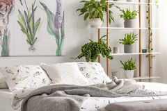 Urban jungle bedroom interior with plants in pots beside a bed dressed in organic cotton linen of white color with green print. Re stock image
