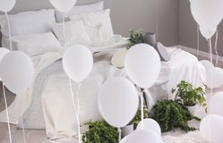 Urban jungle and bunch of white balloons in trendy bedroom with king size bed with white bedding and grey blanket royalty free stock photography