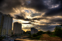 Urban landscape. Dark clouds and sun over the houses Stock Photos
