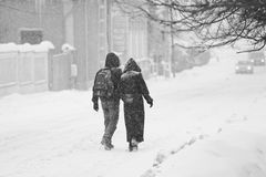 Urban landscape with couple walking in the snow royalty free stock image