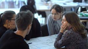 Urban landscape designers sitting by blueprint and talking about building model design irrl.