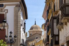Urban landscape of Spanish church through buildings royalty free stock photo