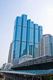 Urban life in CBD area. Urban life in the heart of CBD area of Bangkok. High rise and modern buildings in shade of blue, skytrain on the way Royalty Free Stock Images