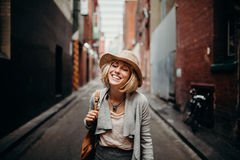 Urban life portrait of smiling woman in the middle of a narrow street in Melbourne, Australia. Smiling woman with casual clothes and a wig having fun in the Royalty Free Stock Photos