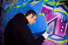 Urban lifestyle. Young man painting on a wall stock photo