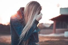 Urban lifestyle. Blond woman wearing jeans jacket standing outdoors in mild sunset light, autumn fashion of youth, urban lifestyle concept stock images