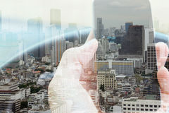 Urban lifestyle and Business technology concept. Double exposure of man using smart phone and cityscape background, urban lifestyle and Business technology royalty free stock images