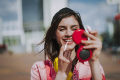 Pretty smiling hipster girl refreshing make up royalty free stock images
