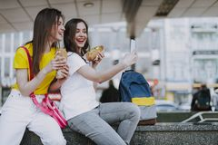 Happy female friends making selfie with hot dogs royalty free stock photography