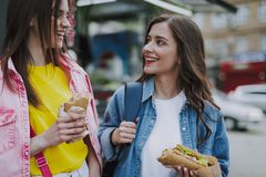Two happy female friends walking with hot dogs stock photo