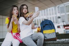 Two female friends making selfie with hot dogs royalty free stock photos