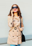 Urban lifestyle fashion portrait smiling young woman talking on smartphone wearing a coat and handbag clutch stands over grey Stock Images