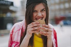 Pretty hipster girl hungrily eating hot dog royalty free stock photo
