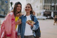 Cheerful girls walking around eating hot dogs stock photo