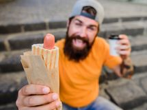 Urban lifestyle nutrition. Carefree hipster eat junk food while sit on stairs. Hungry man snack. Junk food. Guy eating. Hot dog. Man bearded bite tasty sausage royalty free stock image