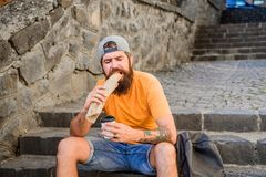 Urban lifestyle nutrition. Carefree hipster eat junk food while sit on stairs. Hungry man snack. Junk food. Guy eating. Hot dog. Man bearded bite tasty sausage stock photo
