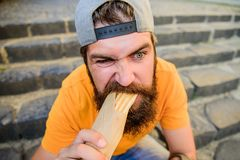 Urban lifestyle nutrition. Junk food. Carefree hipster eat junk food while sit stairs. Guy eating hot dog. Snack for. Good mood. Unleashed appetite. Street food stock image