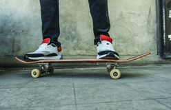 Urban lifestyle portrait crop of man foot on sport sneakers riding skate board on grunge street corner in city life concept. Urban lifestyle portrait crop of men royalty free stock photo