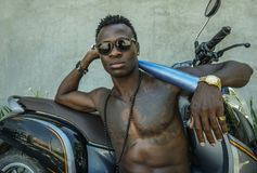 Urban lifestyle portrait of fit body and dangerous looking black afro American man with naked torso and sunglasses sitting on. Urban lifestyle portrait of fit stock photo
