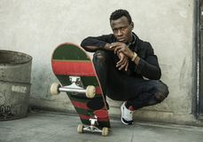 Urban portrait of young attractive and serious black afro American man with skate board squatting on street corner looking cool. Urban lifestyle portrait of royalty free stock photography