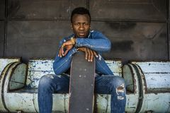 Young handsome and attractive black African American skateboarder man sitting on city grunge bench holding skate board posing in stock image