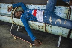 Urban lifestyle portrait of young handsome and attractive black afro American skateboarder man lying on city grunge bench holding. Urban lifestyle portrait of stock image