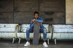 Urban lifestyle portrait of young handsome and attractive black afro American skateboarder man sitting on city grunge bench. Urban lifestyle portrait of young royalty free stock photo