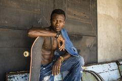 Urban lifestyle portrait of young handsome and attractive black afro American skateboarder man sitting on city grunge bench. Urban lifestyle portrait of young royalty free stock images