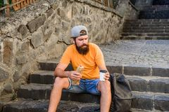 Urban lifestyle and unhealthy nutrition. Carefree hipster eat junk food while sit on stairs. Hungry man snack. Junk food. Guy eating hot dog. Man bearded enjoy royalty free stock image