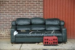 Urban Living Room. Old sofa on the sidewalk with a plastic milk crate ottoman being used by street people Stock Images