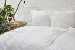 Urban loft bedroom white bed linen and creative nighstand with plants Royalty Free Stock Photo