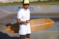 Urban longboarding in concrete skatepark. Close view of skater in sunglasses and baseball cap with smartphone in his hand, listening music through earplugs Stock Photography
