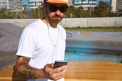 Urban longboarding in concrete skatepark. Closeup on surfer in trucker cap and sunglasses, walking with his longboard in hand and looking at his smartphone while Stock Image