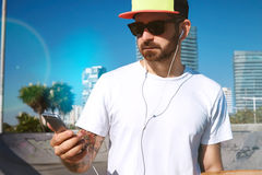 Urban longboarding in concrete skatepark. Closeup on surfer in trucker cap and sunglasses, wearing white blank t-shirt and looking at his smartphone while Royalty Free Stock Photos