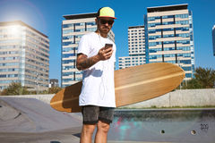 Urban longboarding in concrete skatepark. Skater in sunglasses and baseball cap looking at his smartphone and listening music through earplugs headphones Royalty Free Stock Photography