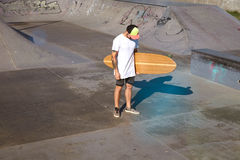 Urban longboarding in concrete skatepark. Unrecognizable tattooed skater in trucker cap stands in unlabeled blank white t-shitrt with his bamboo longboard in Royalty Free Stock Images