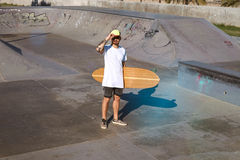Urban longboarding in concrete skatepark. Young attractive tattooed skater holds hand on trucker cap and stands in plain blank white t-shitrt with his handmade Stock Image