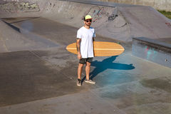 Urban longboarding in concrete skatepark. Young attractive tattooed skater in trucker cap stands in unlabeled blank white t-shitrt with his wooden longboard in Stock Photo