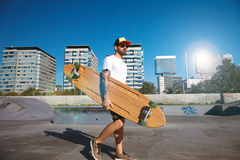 Urban longboarding in concrete skatepark. Young attractive tattooed skater in trucker cap walks in unlabeled blank white t-shitrt with his wooden longboard in Royalty Free Stock Photo