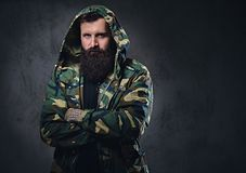 Urban look bearded male with crossed arms dressed in a camouflage jacket. Urban look bearded male with crossed arms dressed in a camouflage jacket on grey Stock Photo