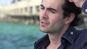 Urban Male Combing Hair Near Ocean. Stock video of man combing hair stock footage