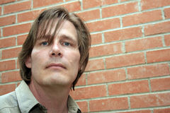 Urban Man. Man in late thirties/early forties with longish hair and earring,serious expression. Set against background of brick wall. Room for text or cropping Stock Images